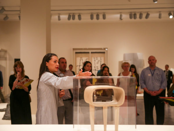 A curator gestures toward a contemporary sculpture in front of a crowd of visitors