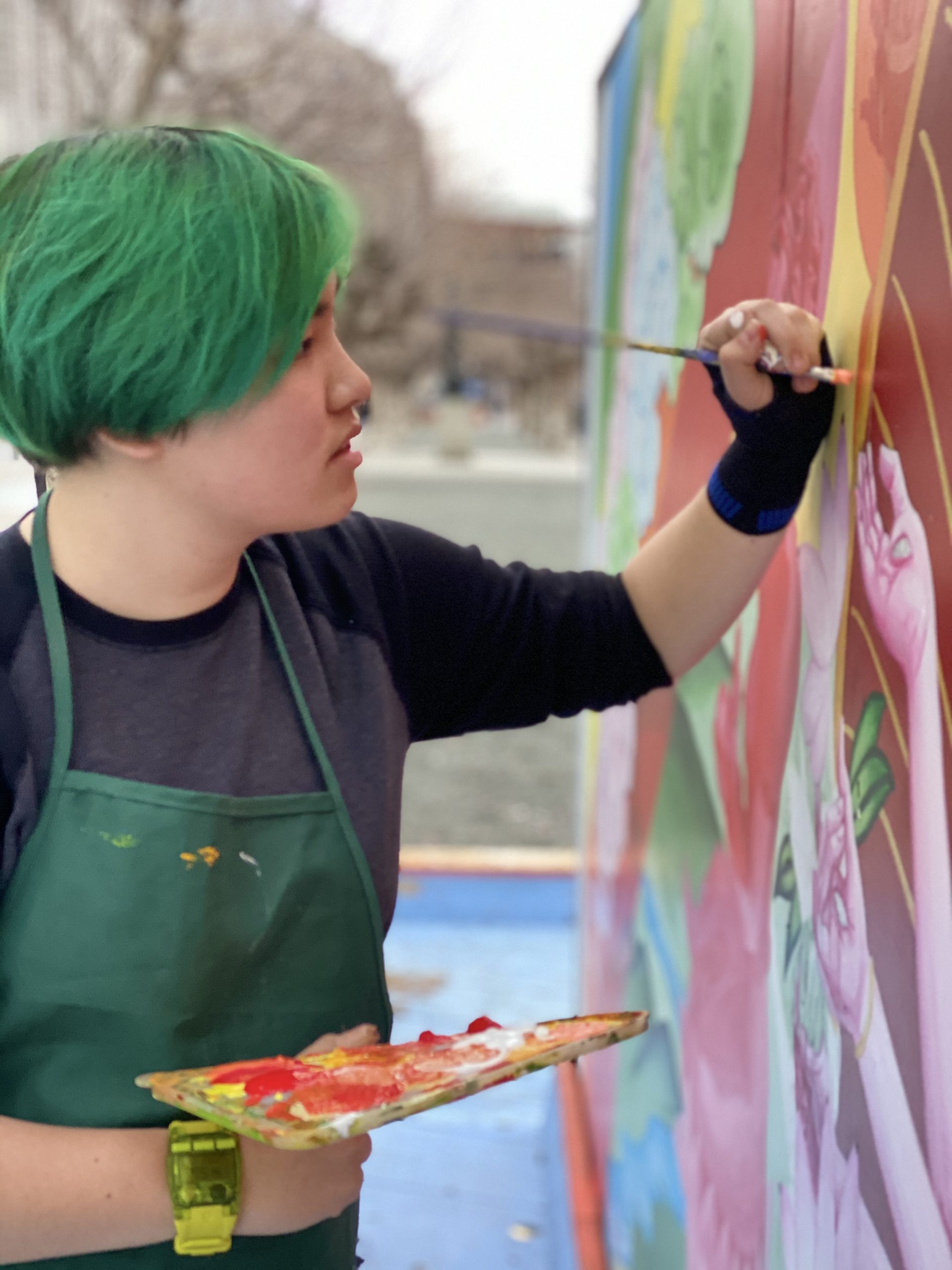 An artist with short green hair paints a colorful mural.