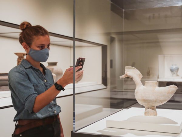 Woman reads information on cell phone while standing in front of a vessel shaped like a duck.