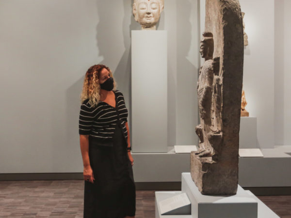 A woman wearing a mask looks at a stone statue.